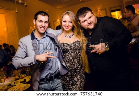 Odessa, Ukraine December 31, 2015: People smiling and posing on cam during concert in night club party. Man and woman have fun at club. Boy and girl at night club party