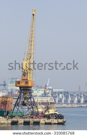 Odessa, Ukraine - July 26, 2015: Cargo cranes on rails and cargo warehouses in the seaport. Port of Odessa is the largest Ukrainian seaport with annual traffic capacity of 40 million tonnes