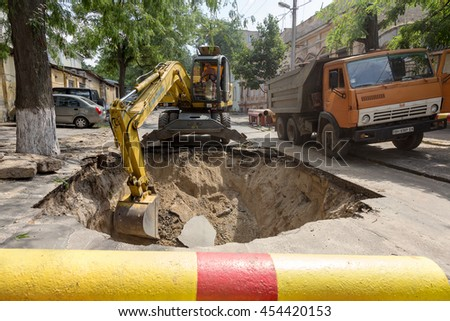 Odessa, Ukraine - July 18, 2016: Emergency repair work of main urban heat pipes. Working tractor excavator digs a pit trench at site of heating failure. Closed road for passage of vehicles