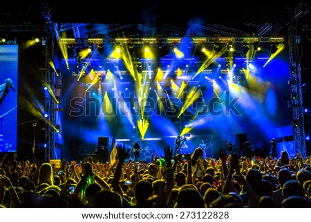 Odessa, Ukraine - June 28, 2014: A large crowd of people having fun at stadium, at a concert of Ukrainian group Okean Elzy during the creative light and music show. Cheerful bright show at club party