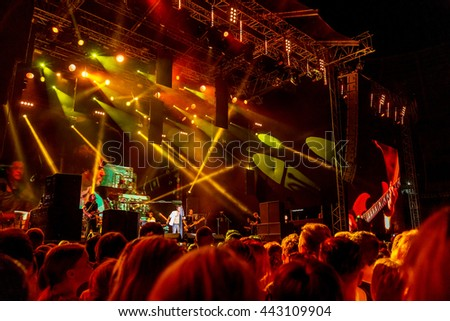 Odessa, Ukraine - June 25, 2016: A large crowd of spectators having fun at stadium, at concert of Ukrainian group Ocean Elzy during creative light and music show. Cheerful bright show in party club