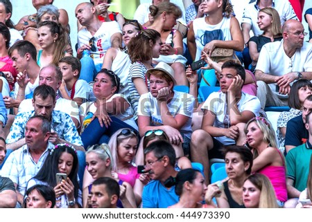 Odessa, Ukraine - June 25, 2016: crowd of spectators at concert during  creative light and music show. Crowds and queues of people on face-control, spectators in stands and field. People relaxing fun