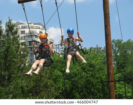Odessa, Ukraine - June 6, 2016: Extreme swings in amusement park - the people on the course in the mountain helmet and safety equipment. Active holidays.