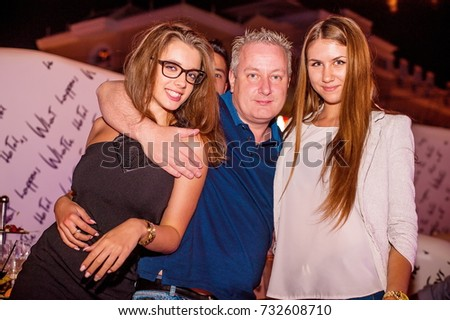 Odessa, Ukraine June 27, 2015: Ibiza club. People smiling and posing on cam during concert in night club party. Man and woman have fun at club. Boy and girl at night club party