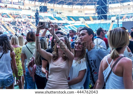Odessa, Ukraine - June 25, 2016: large crowd of spectators having fun at stadium, at concert of Ukrainian group Ocean Elzy during creative light and music show. Cheerful bright show in the party club