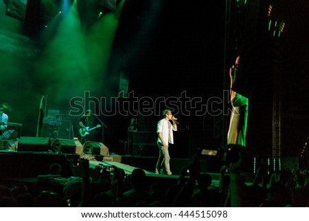 Odessa, Ukraine - June 25, 2016: large crowd of spectators having fun at the stadium, at concert of Ukrainian group Ocean Elzy during creative light and music show. Cheerful bright show in party club