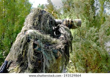 Odessa, Ukraine - June 15, 2011: Military exercises of Border Troops of Ukraine, the military sniper in camouflage clothing ambush looking through binoculars June 15, 2011 in Odessa, Ukraine. - stock photo