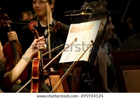"Odessa, Ukraine -  June 09, 2013: Symphonic orchestra of conductor performs on stage playing instruments music. ""International Festival of Arts"" Odessa National Theater of Opera and Ballet."