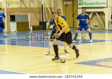Odessa, Ukraine - June 2, 2015: Unidentified players local teams playing in  tournament of mini-football in  futsal on parquet floor. Poor lighting in an inexpensive futsal. Men spend leisure, Hobbies