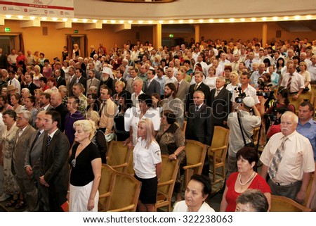 Odessa, Ukraine - June 25, 2010: Zritelnny Hall Concert Hall. Spectators before the solemn meeting and a concert. Spectators stot during the anthem of the state. The audience in the hall.