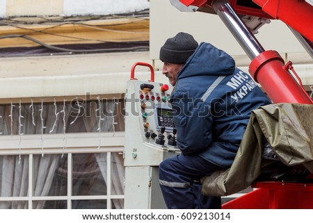 ODESSA, UKRAINE - MARCH 26, 2017: Rescuers on fire truck from fire staircase eliminate consequences of collapse of part of house as result of an earthquake. Ruined old house, consequences of earthquake