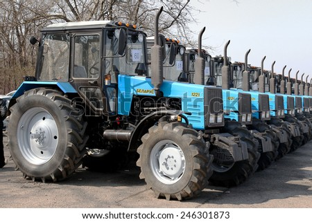 ODESSA, UKRAINE - 31 March 2011: The new agricultural tractors of various models stand in a row at the exhibition site in readiness for the start of spring sowing of agricultural