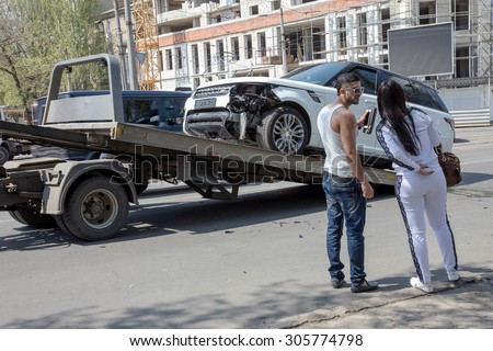 Odessa, Ukraine - May 3, 2015: A car accident in the city center. expensive car was loaded onto a tow truck after a car accident. The driver and passenger sad look at the work truck. - stock photo
