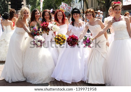 ODESSA, UKRAINE - MAY 26: Annual event Bride Parade. Happy excited participants in fiancee`s gowns take part in celebration of marriage and romance Bride Parade on May 26, 2013 in Odessa, Ukraine - stock photo
