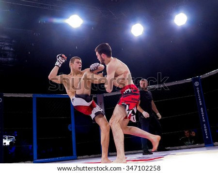 """Odessa, Ukraine - 24 November 2015: Athletes in the ring extreme Sport mixed martial arts competition tournament series  """"World MMA Network � MAXMIX"""". The dramatic moment of battle punches - stock photo"""