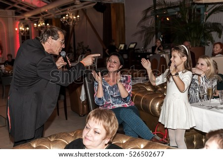 ODESSA, UKRAINE -28 November2016: Concert Tribute show Adriano Celentano. Soloist of musical group - Adolfo Sebastiani - known singer, showman Celentano. Among tables with audience concert-hall double