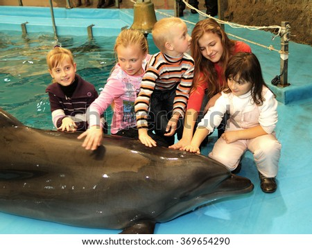 ODESSA, UKRAINE - NOVEMBER 26, 2011: Happy young children carefully and emotionally watching presentation dessirovannyh dolphins dolphins in the city.