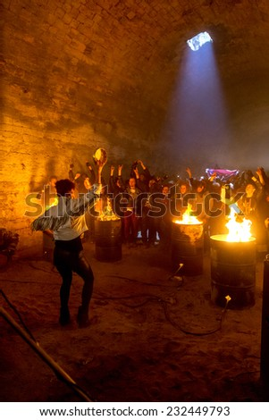 Odessa, Ukraine - November 22: Local rock band plays rock concert in the underground catacombs dungeon destroyed building. A crowd happy people, fans campfire enjoy, November 22, 2014 Odessa, Ukraine