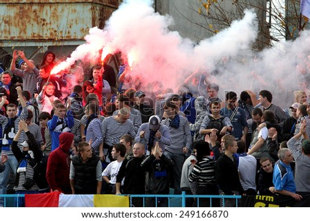 Odessa, Ukraine - November 14, 2010: Ultras emotional football fans during the game for his club Chernomorets rioted with police, broken rostrum, fights, fireworks on the playing field - stock photo