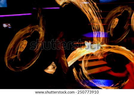 Odessa, Ukraine -15 October 2010: Abstract bright streaks in the air from the movement of lights during an unusual fire dance show during the presentation in a nightclub at a party