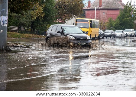 ODESSA, UKRAINE - 21 October 2015: As a result of heavy rains flooded the streets of big puddles. Cars traveling in the rain on a wet road heavily sprayed water and dirt - stock photo