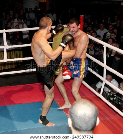 Odessa, Ukraine - October 14, 2010: Fight Club. Fighting without rules. Mixed martial arts fighters compete in the cell, resulting in punches and kicks. The dramatic moment of the battle.