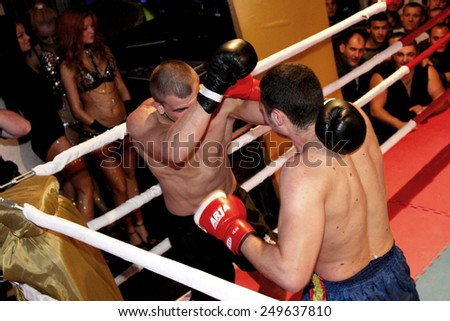 Odessa, Ukraine - October 14, 2010: Fight Club. Fighting without rules. Mixed martial arts fighters compete in the cell, resulting in punches and kicks. The dramatic moment of the battle. - stock photo