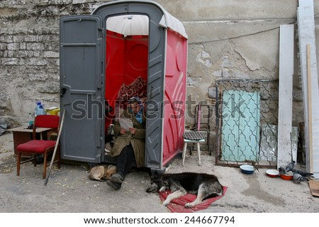Odessa, Ukraine, 29 October 2008: Homeless elderly woman lives in platikovom outdoor toilets, surrounded by dogs, October 29, 2008 in Odessa, Ukraine - stock photo