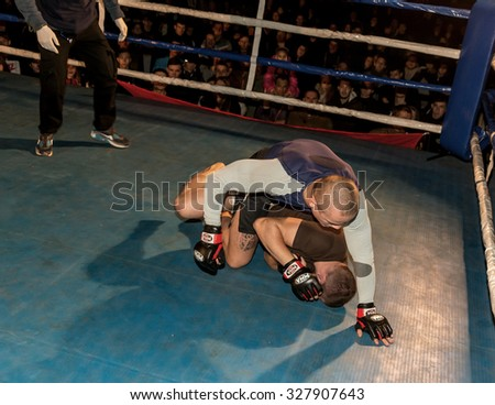 Odessa, Ukraine - October 14, 2015: Regional fights in the ring. Athletics MMA mixed martial arts fighters to compete, resulting in the throws and punches and kicks. The dramatic moment of the battle