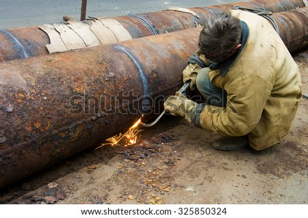 ODESSA, UKRAINE - 09 October 2015: Welder welds pipe segments. Repair and replacement of outdated pipes in the city center.