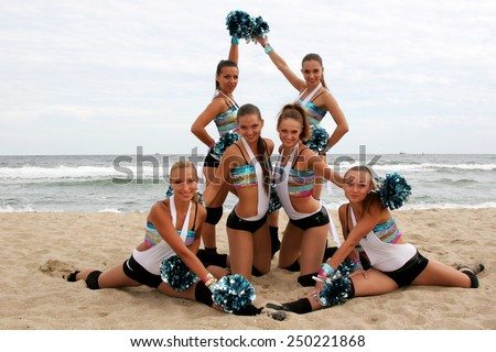 Odessa, Ukraine - September 4, 2010: Bright dynamic performance of women's support group sports team on the sandy shores of Black Sea. Cheerleaders in Aktion. Bright beautiful young girl in sportswear