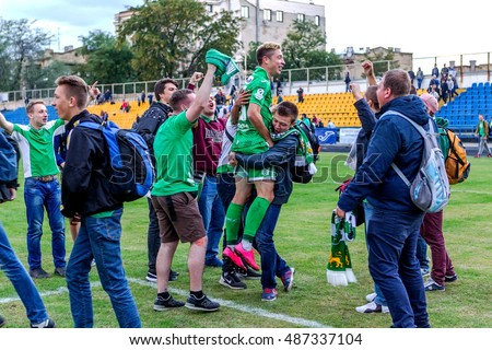 ODESSA, UKRAINE - September 21, 2016: Football fans and the stadium audience emotionally support their team. Hooliganism spectators ran onto the football field. Violation of the rules of the game