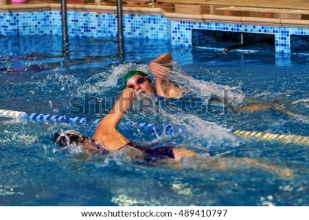 ODESSA, UKRAINE -24 September 2016: sporting swimming in pool during Ukrainian championship triathlon athletes among children. Children swimming competition in indoor pool