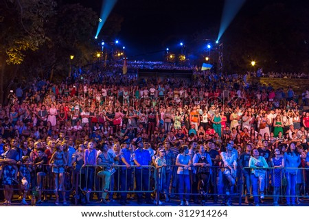 Odessa, Ukraine - September 2, 2015: The audience at concert during the creative light and music show fashionable jazz band. Night scene, audience emotionally watching, standing outside on stairs - stock photo
