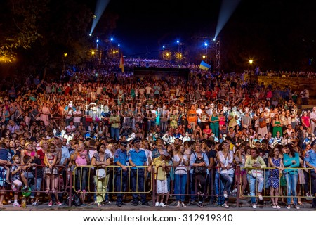 Odessa, Ukraine - September 2, 2015: The audience at concert during the creative light and music show fashionable jazz band. Night scene, audience emotionally watching, standing outside on the stairs - stock photo