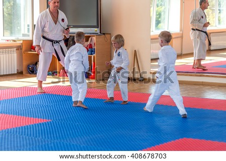 ODESSA, UKRAINE - 1 September 2015: The boys of younger age at a sporting event in gym struggling to sports mats. Kids karate competitions. Children's sports hall