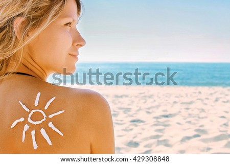 of sun cream on the female back on the beach - stock photo