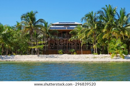 Off-grid beach house with solar panels on the roof and tropical vegetation on an island of the Caribbean sea, Panama - stock photo