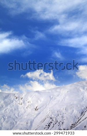 Off-piste slope and blue sunlight sky with clouds. Caucasus Mountains, Georgia, ski resort Gudauri.