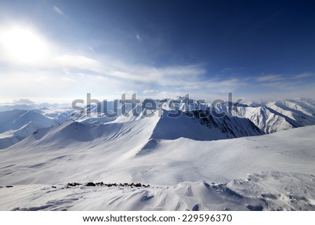 Off-piste slope and sky with sun. Caucasus Mountains, Georgia, ski resort Gudauri. Wide angle view. - stock photo