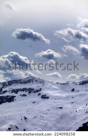 Off-piste slope and sunlight clouds. Caucasus Mountains, Georgia, ski resort Gudauri. - stock photo