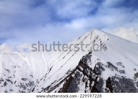 Off-piste slope in morning and sky with clouds. Caucasus Mountains, Georgia, ski resort Gudauri. - stock photo