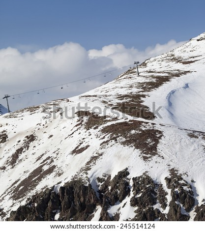 Off-piste slope with stones and chair-lift in little snow year. Caucasus Mountains, Georgia, ski resort Gudauri. - stock photo