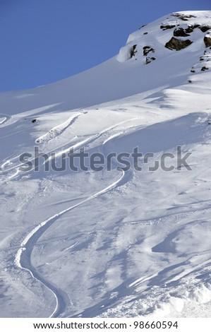 Off-piste snowboard track in sunset light - stock photo