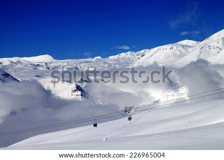 Off-piste snowy slope and cable car at nice day. Caucasus Mountains, Georgia. Ski resort Gudauri. - stock photo