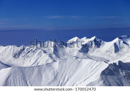 Off-piste snowy slope at sunny day and multicolor blue sky. Caucasus Mountains, Georgia, ski resort Gudauri. - stock photo
