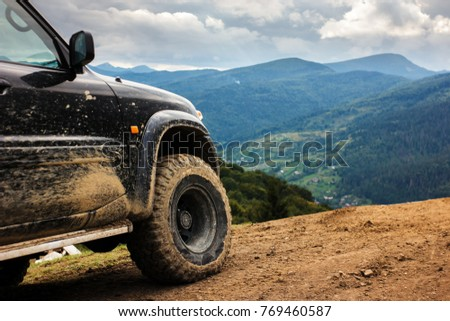 Off road car in mountains. SUV with dirty wheel stands on top of mountain. Travelling by car in Carpathians, Ukraine