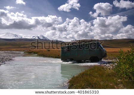 Off-road car moving mountain river at a ford on the background of snowy peaks, Plateau Ukok, Altai mountains, Siberia, Russia - stock photo