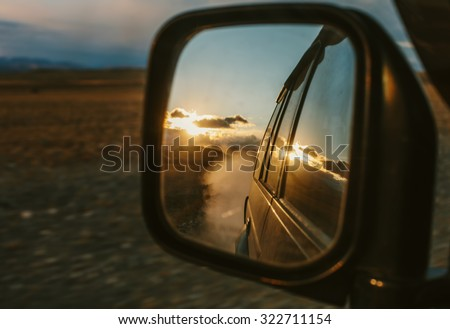 Off-road Car travel by SUV. Mountain Road, clouds and sunset reflecting in mirror. Trip, speed, road - stock photo