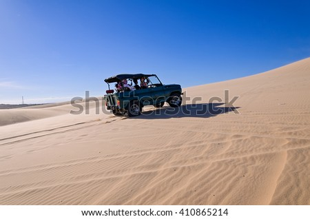 off road car vehicle in white sand dune desert at Mui Ne, Vietnam - stock photo